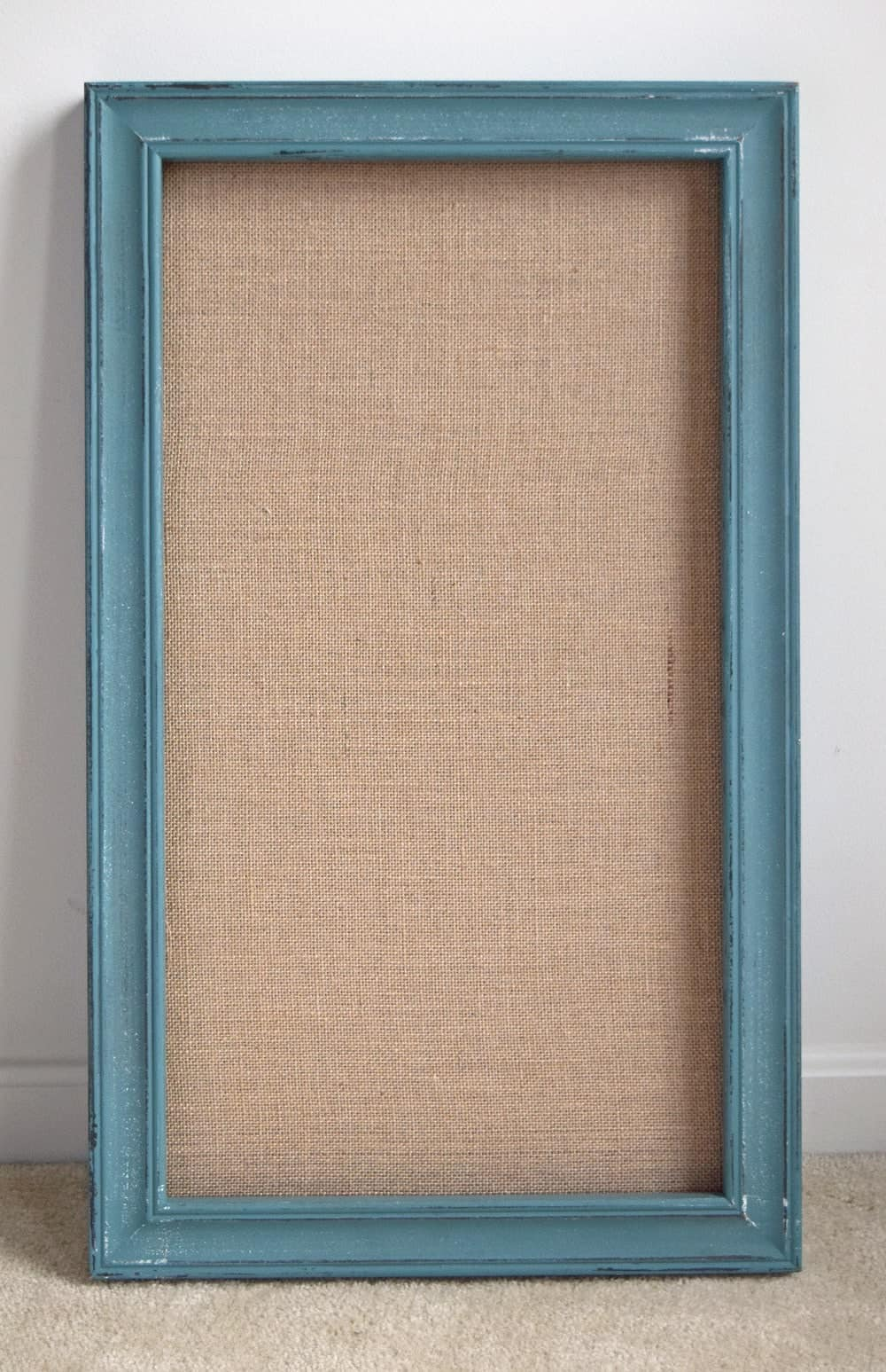 Turquoise painted rectangular frame with burlap backer board propped on white wall.