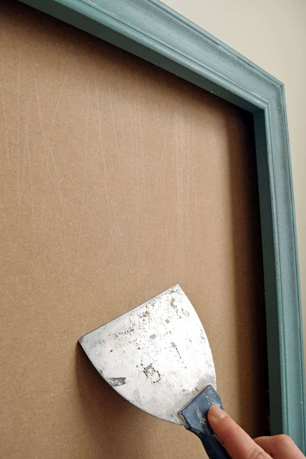 Turquoise wood frame with plane backer board scraped clean with metal putty knife.
