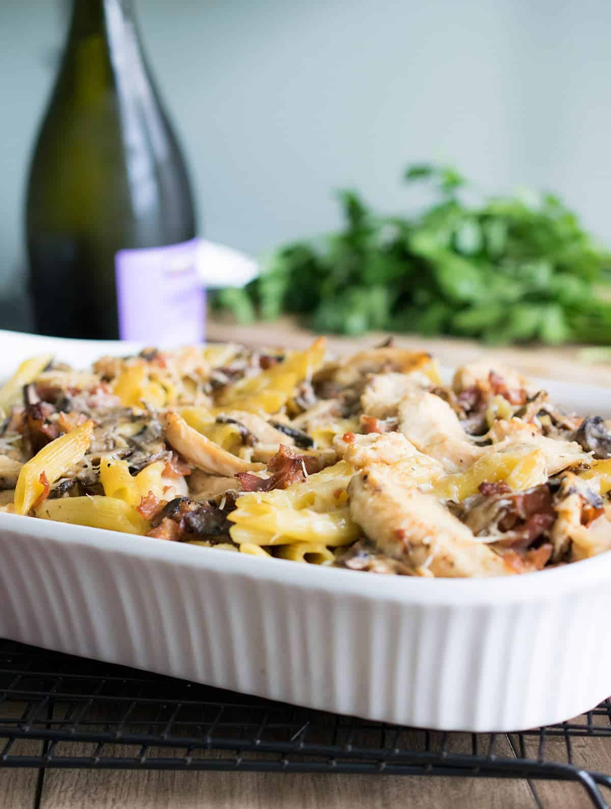 Creamy baked chicken marsala pasta in white bakeware with prosciutto, mushrooms, and parmesan cheese