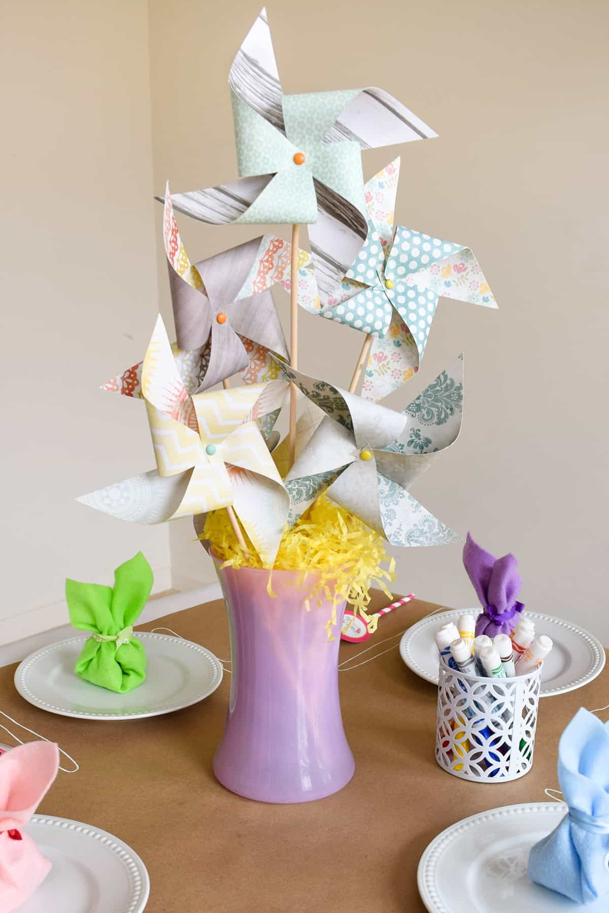 Pinwheel Centerpiece for the dining table with colorful printed pinwheels in purple vase with yellow Easter grass on brown table.