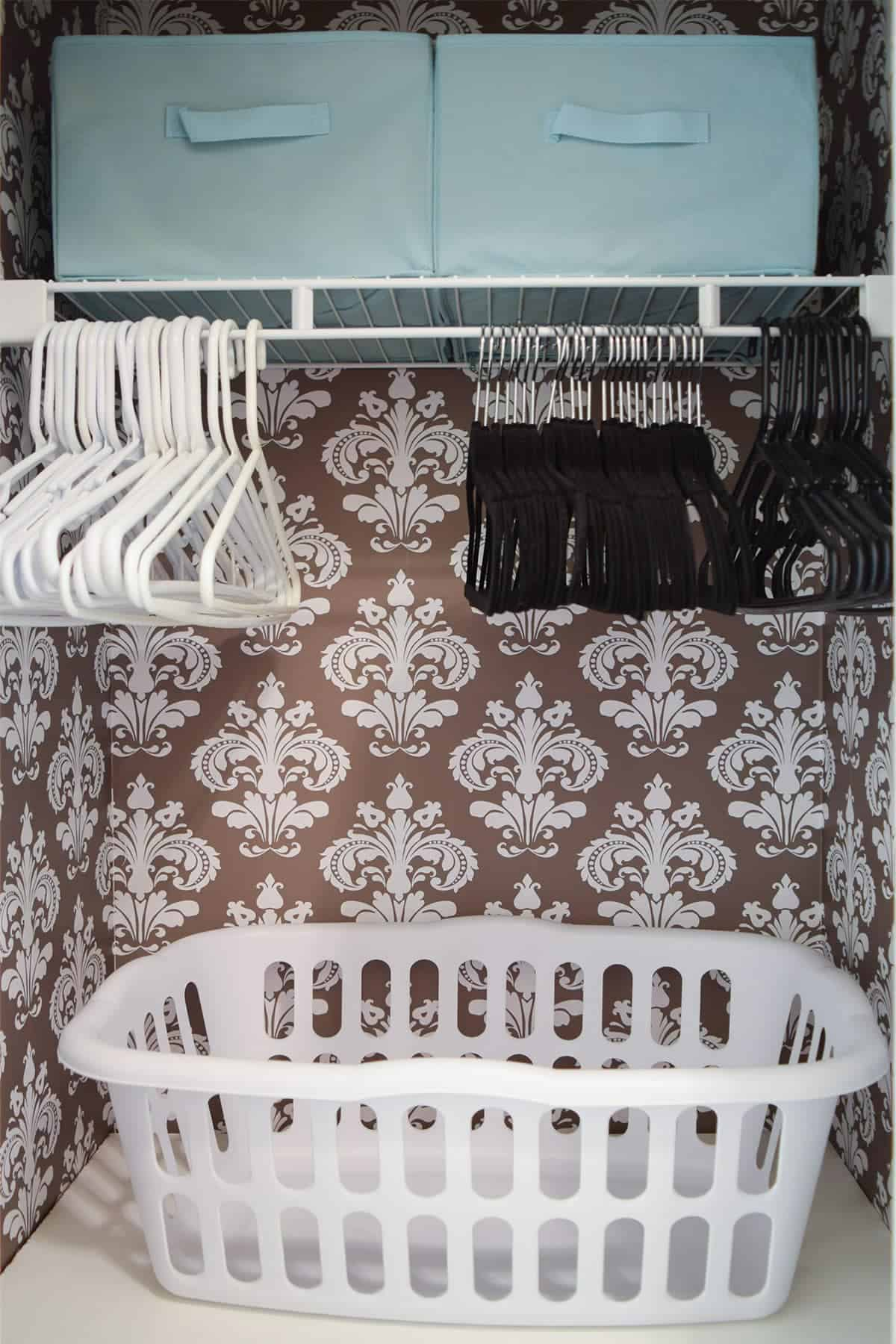 Small laundry closet with brown and white damask wall covering, white shelves with laundry baskets, black and white hangers, and teal bins.