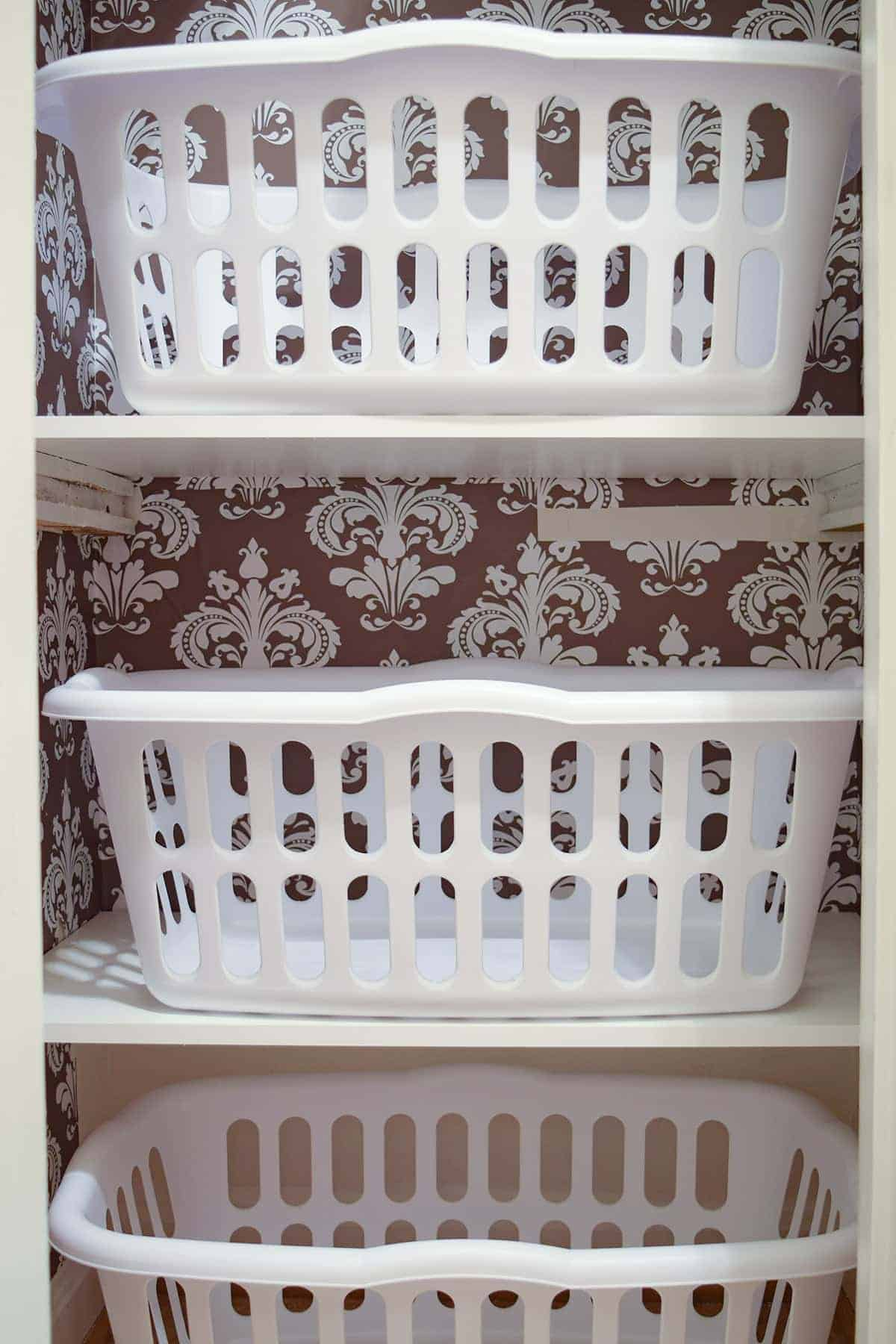 Inside of laundry closet with peel and stick brown and white wall covering, white shelves, and 3 white laundry baskets.