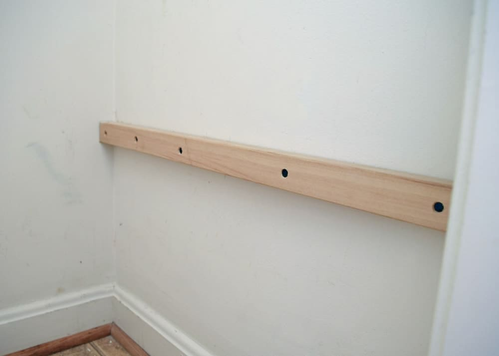 White wall in laundry closet with wooden rail mounted for adding shelves.