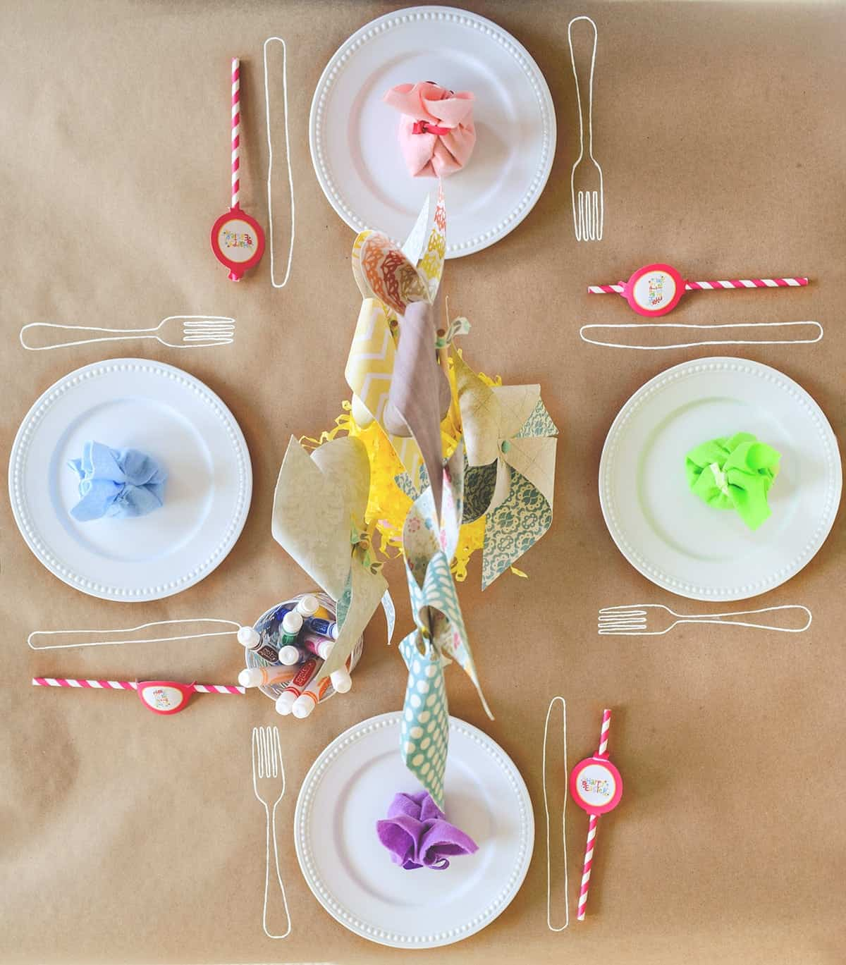 Brown craft paper covering for kid's table with white plates, colorful napkins, pinwheel centerpiece, and markers for drawing on table.
