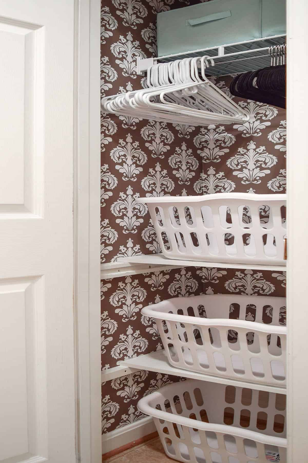 whole laundry closet makeover. This closet with shelves holds laundry baskets for sorting.