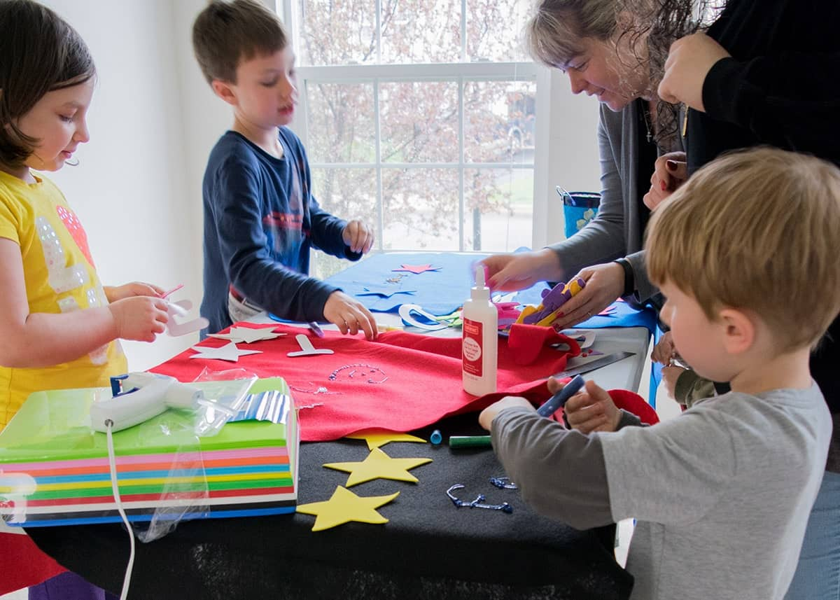 Children around table with fabric cutouts for making Avengers themed party decorations.
