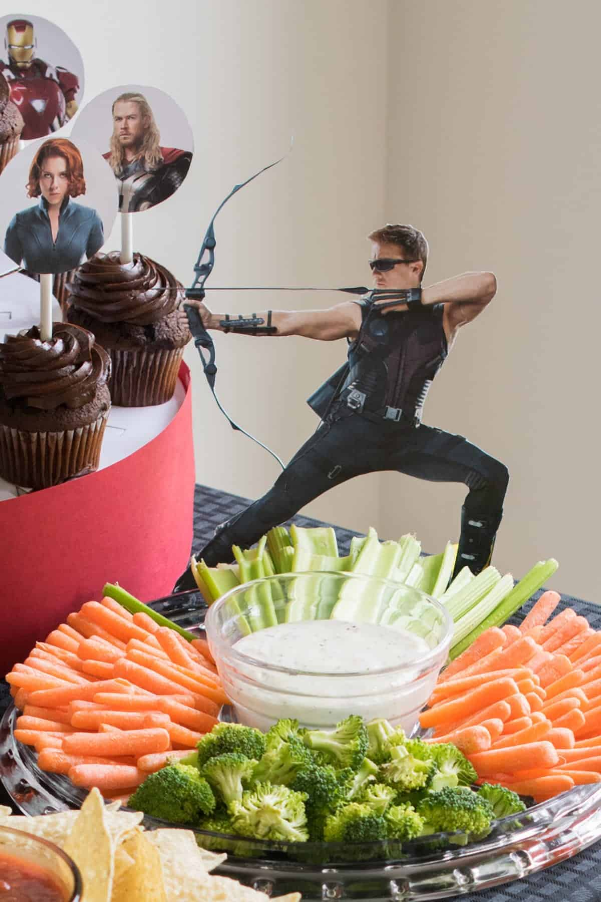 Avengers Party table top with chocolate cupcake display and vegetable tray with character cutout toppers.