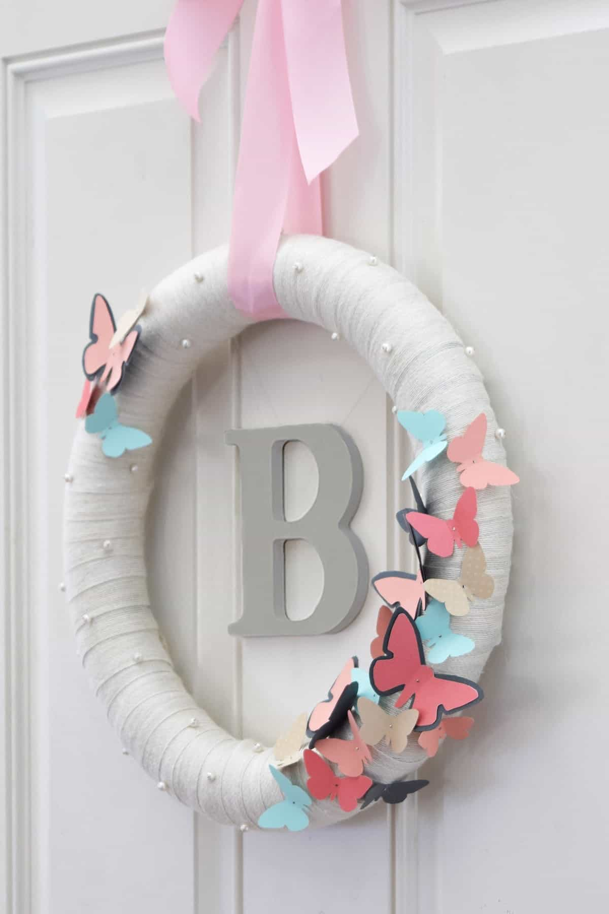 DIY Butterfly Wreath with Monogram on front door. Wrapped white wreath with blue and pink butterflies and pearls on pink ribbon.