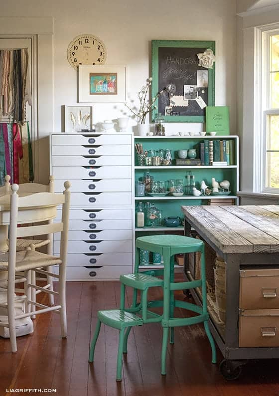 Vintage Craft room with rustic table, green accents, white cabinet, and collection of books and glass collectibles.