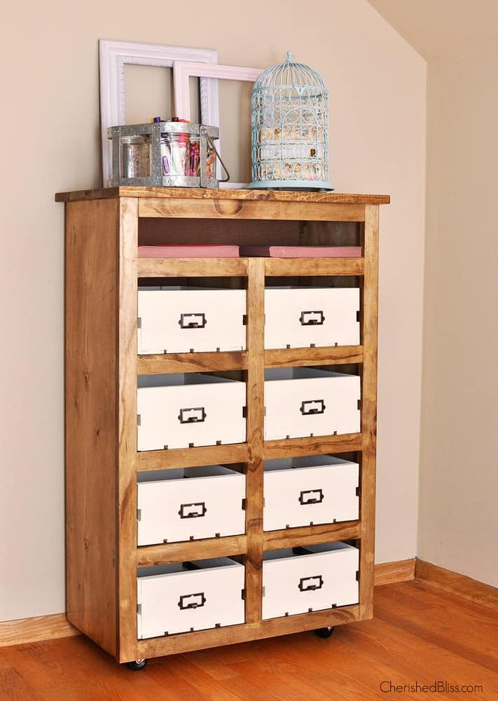 Tall wooden chest with eight white storage bins with empty frames and blue bird cage on top in white room.