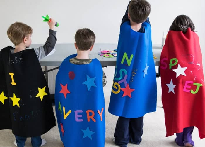 Four children wearing colorful DIY felt superhero capes in front of gray table.