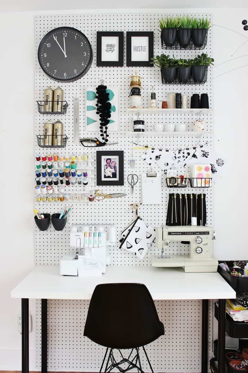 Large white pegboard on white wall with sewing and craft supplies hanging above white desk with sewing machine.