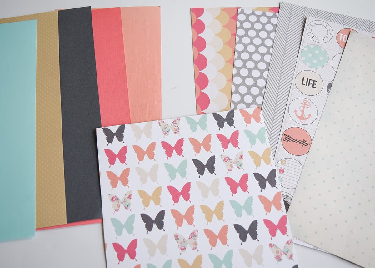 Collection of colorful craft paper with sheet of butterfly printed craft paper on top.
