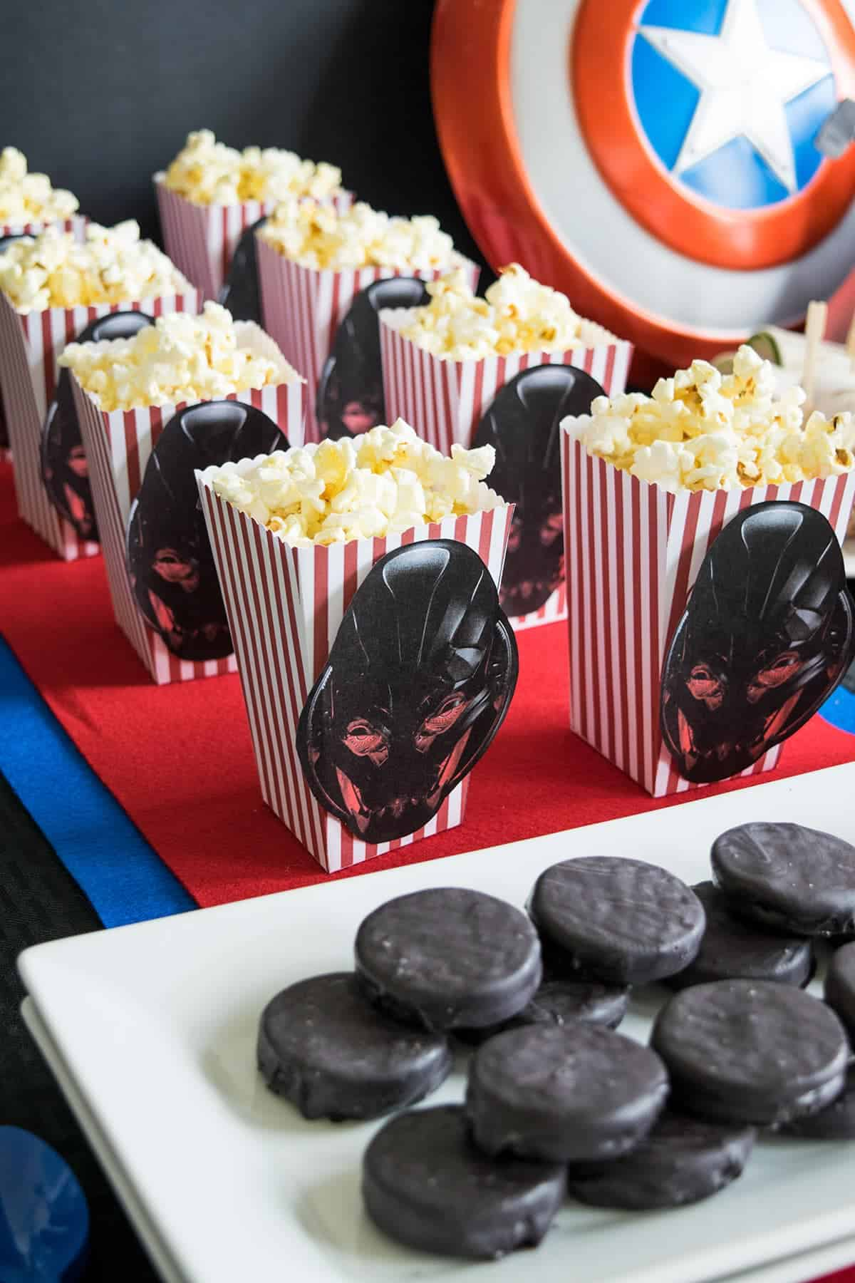 Avengers themed party table with white tray of dipped Oreos, popcorn boxes filled with chips and Ultron character cutouts on front.