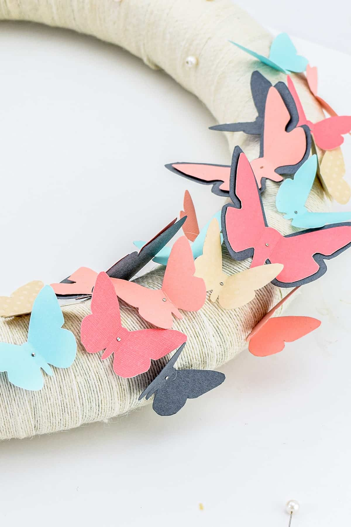 Colorful blue and pink paper butterflies attached to foam ring wrapped with white ribbon.