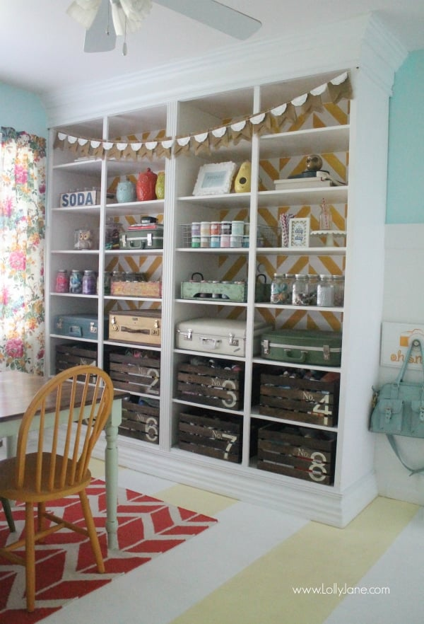 Large white shelving unit with painted crates, colorful antique luggage and assorted jars with stored craft supplies.