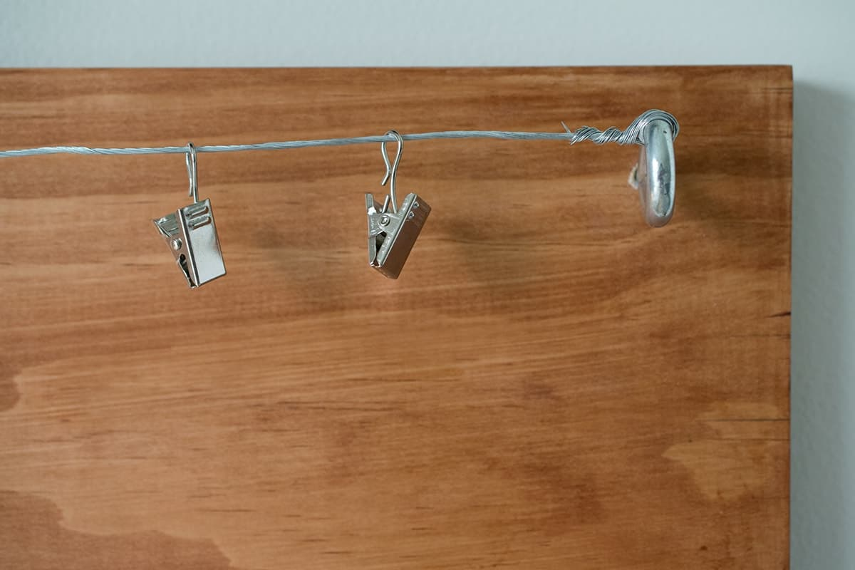 Corner of wooden plank with metal eyelet screwed by edge with attached metal wire and metal hanging clips.