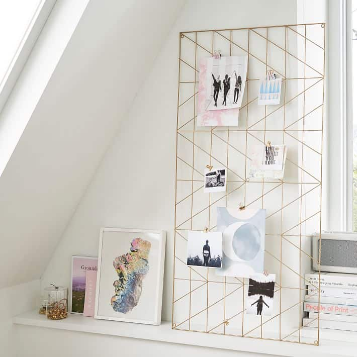 Oversized metal art frame with clips on a desk.