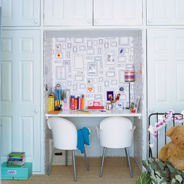 Recessed homework station idea with white table and chairs set in white storage cabinet area.