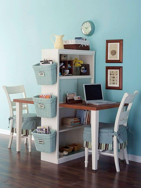 Double sided homework station with white table and chairs, separated by white shelf against bright teal wall.
