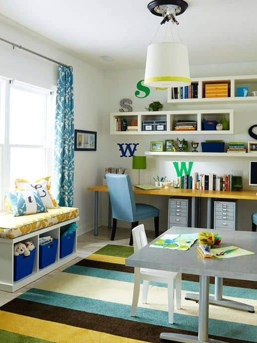 Colorful office with large gray desk, open storage shelves, and large area rug with blue, green, and yellow color palette.