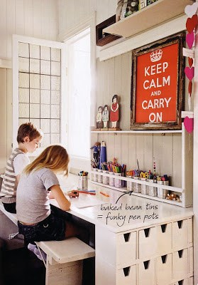 Two children on bench at large white desk in homework station with  storage bins and buckets with school supplies.
