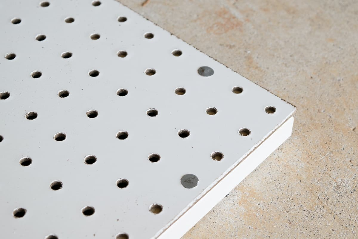 Corner of white pegboard on concrete surface.