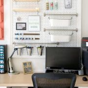 Desk area with large pegboard for craft and office supplies.