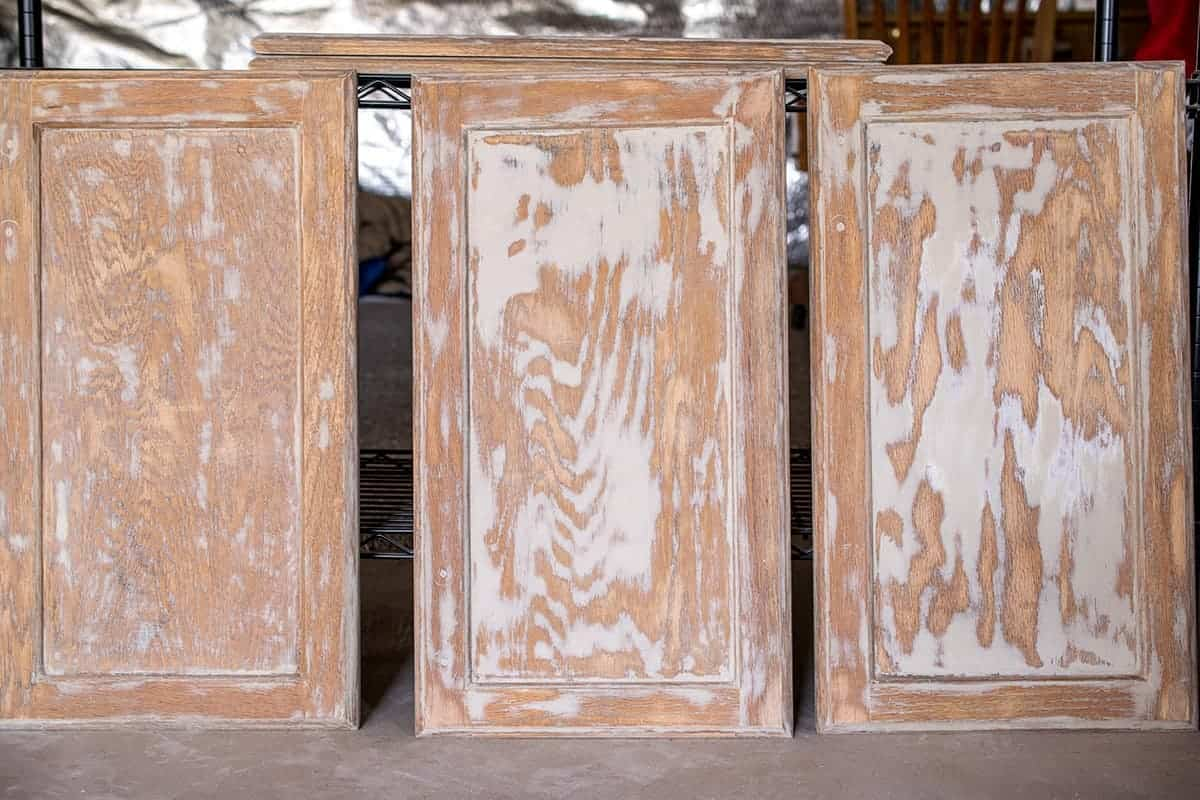 Three cabinet doors upright after sanding and filling wood grain.