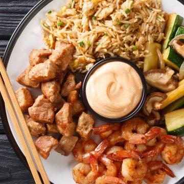 Hibachi Chicken and Shrimp on a plate with yum yum sauce in the center.