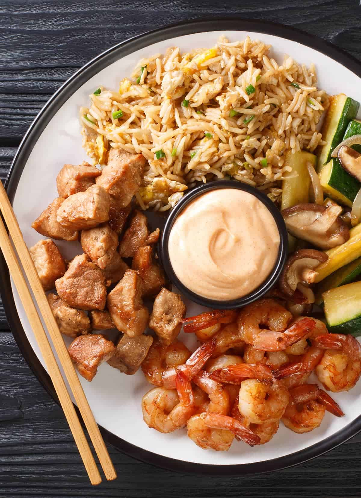 Seasoned shrimp and diced chicken hibachi with zucchini, mushrooms, and fried rice with cup of yum yum sauce on white plate with chopsticks.
