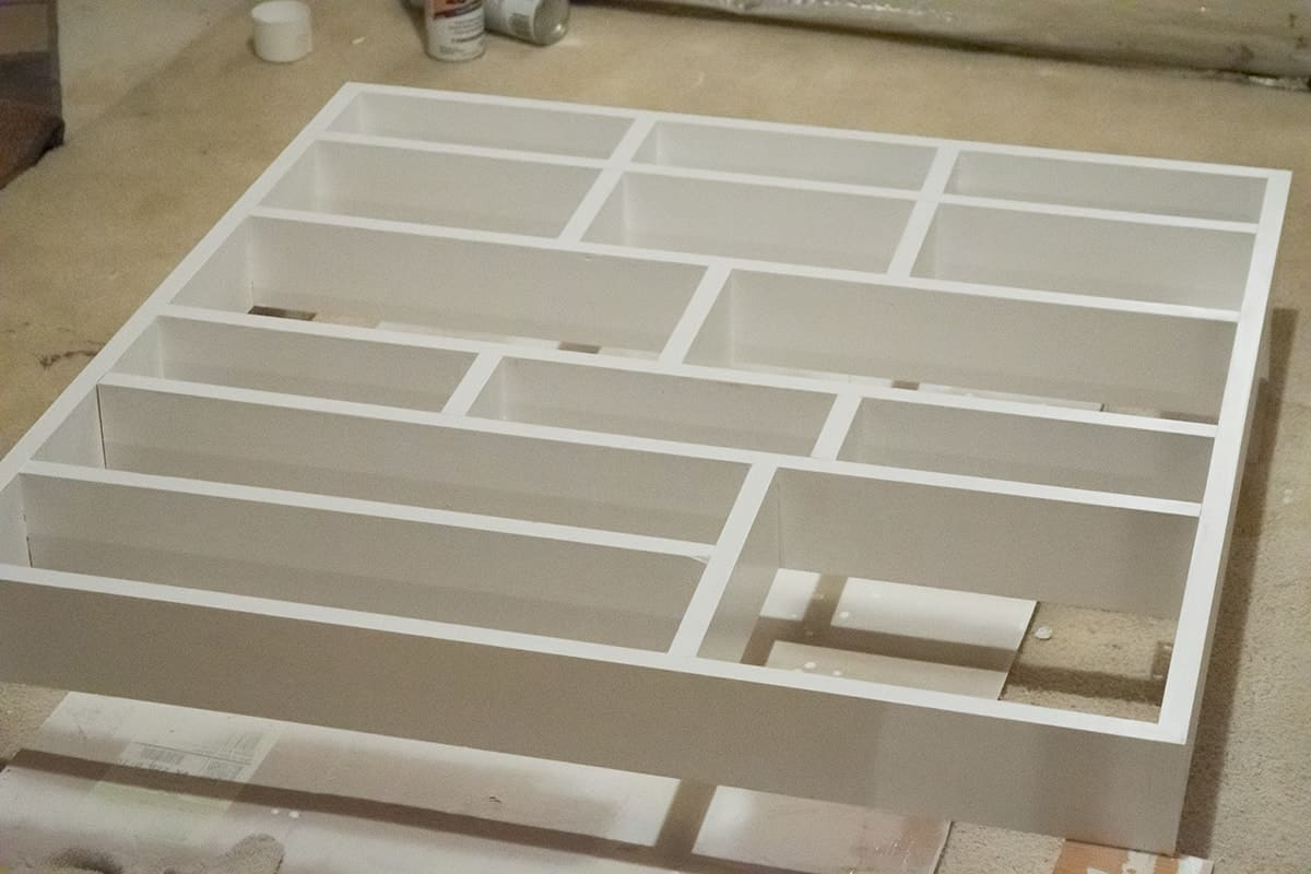 DIY wall shelf with fresh coat of white paint positioned horizontally.