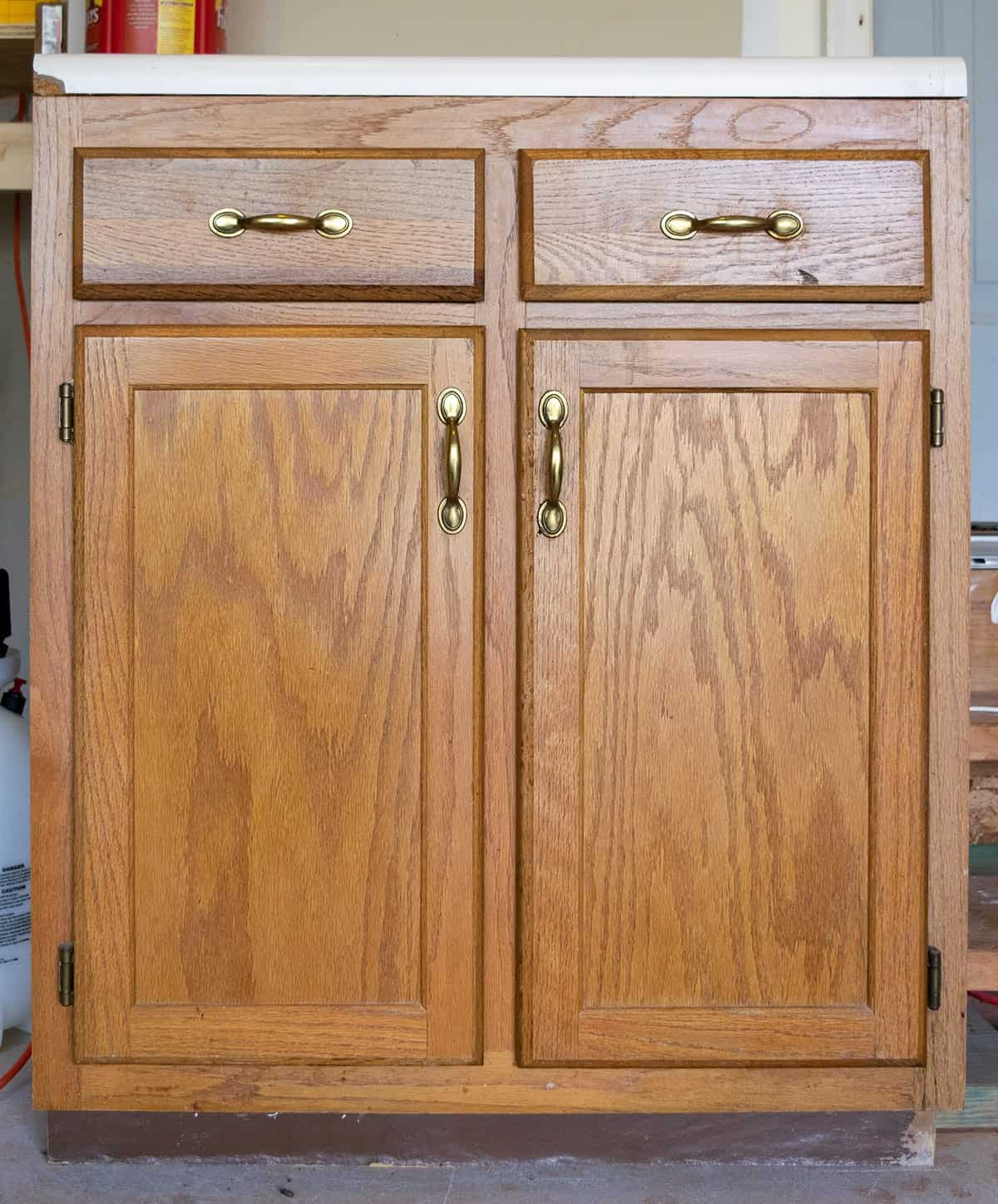 Old oak wood kitchen cabinet section with brass hardware with coffee canister on top.