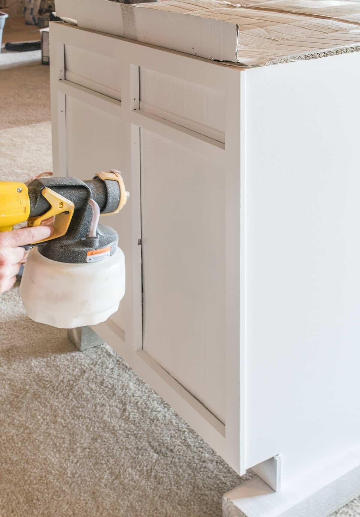 Paint spraying gun applying white matte finish paint to cabinet section.