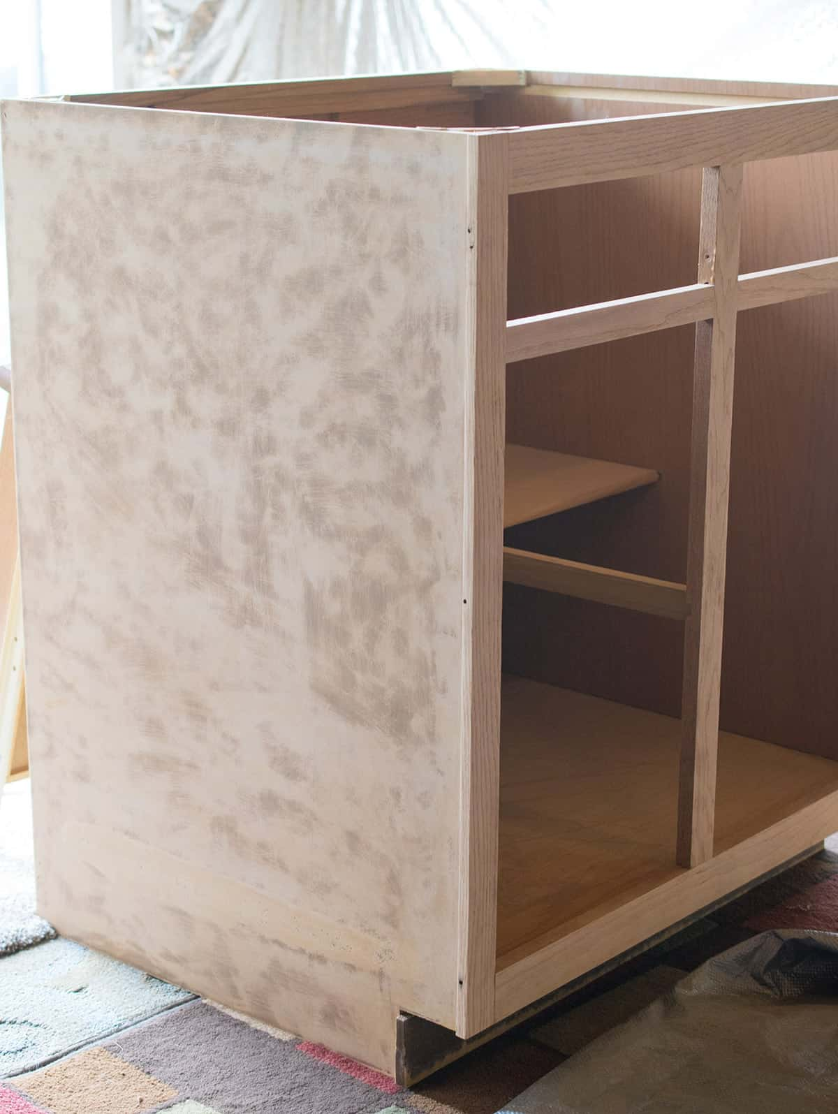 Sanded section of kitchen cabinet with doors and counter removed.
