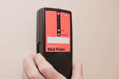 Placing a stud finder on the wall.