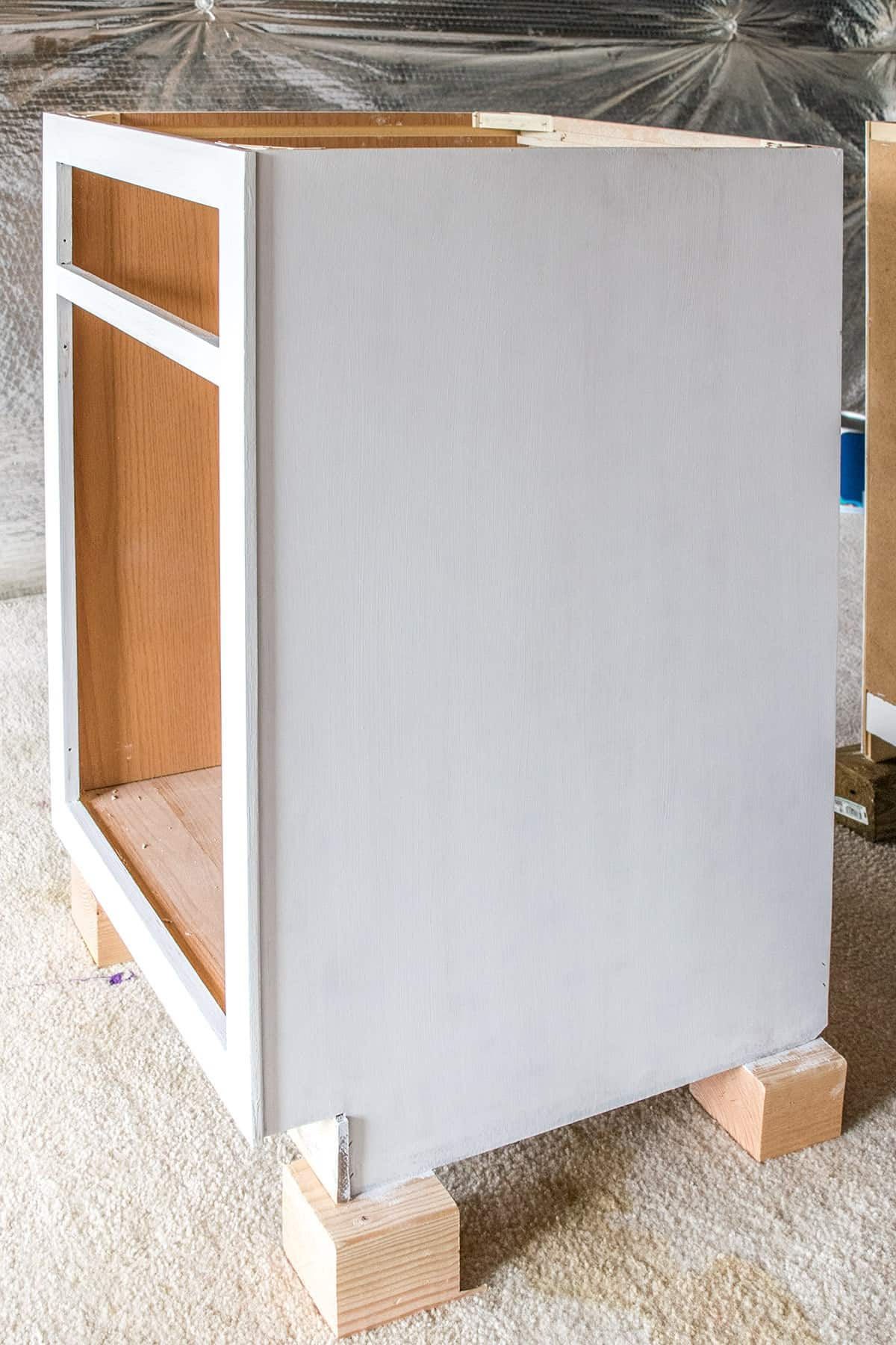 Cabinet section painted white with doors removed, resting on wooden blocks on beige carpet.