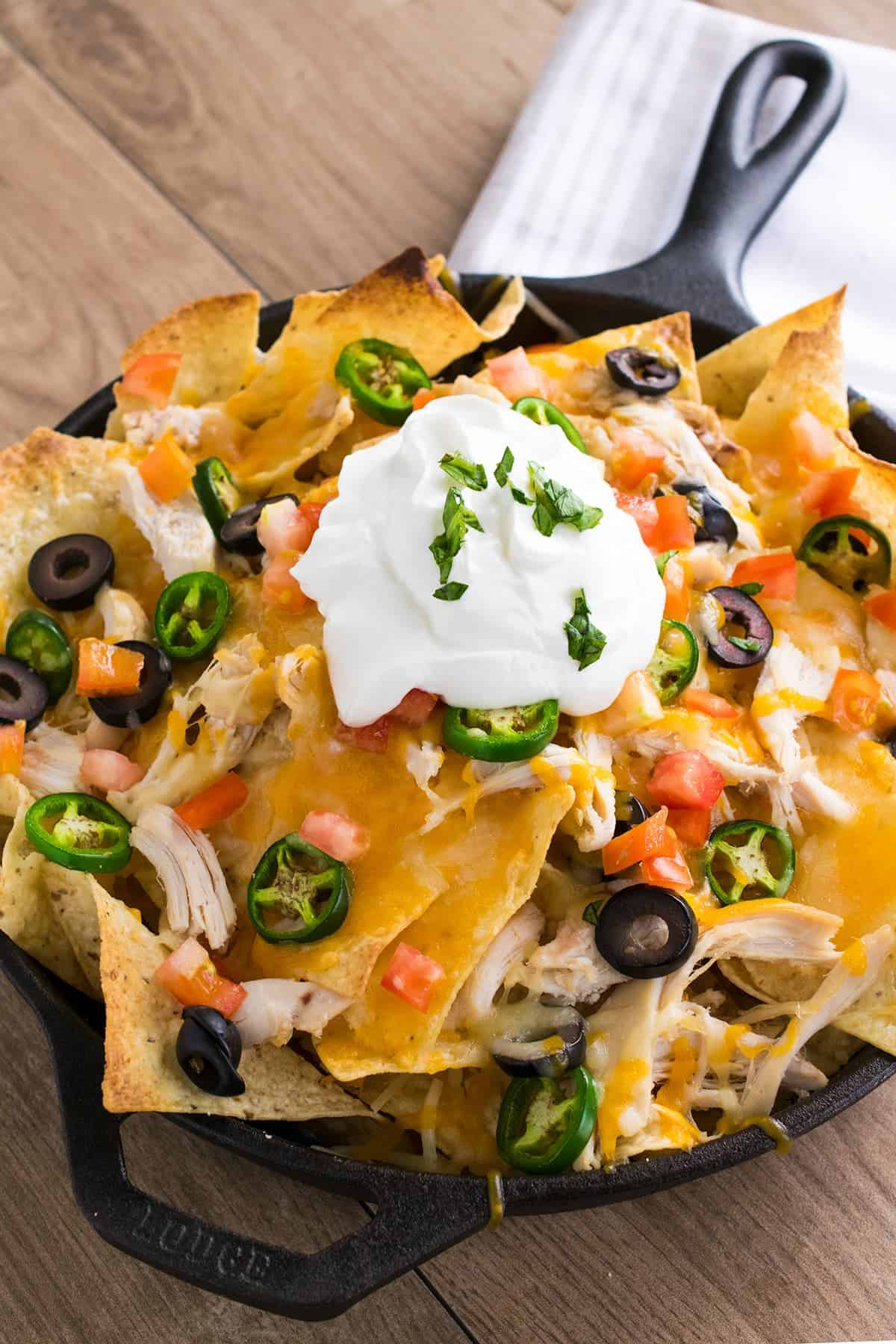 Shredded Chicken Nachos topped with melted cheese, tomatoes, black olives, jalapeno, and sour cream served in cast iron skillet.