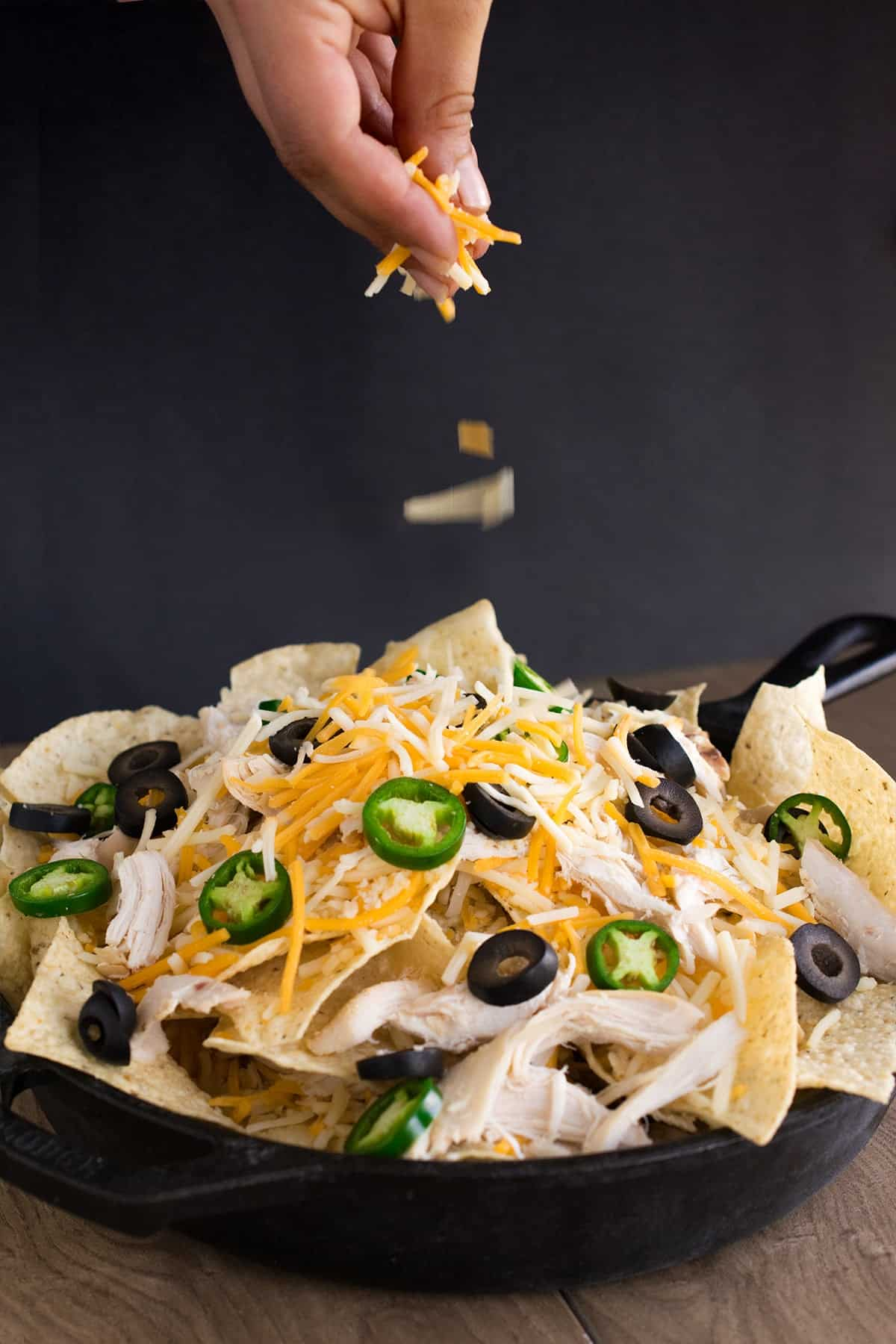 Hand sprinkling shredded cheese on mound of tortilla chips with chicken, jalapenos, and chicken in cast iron skillet.