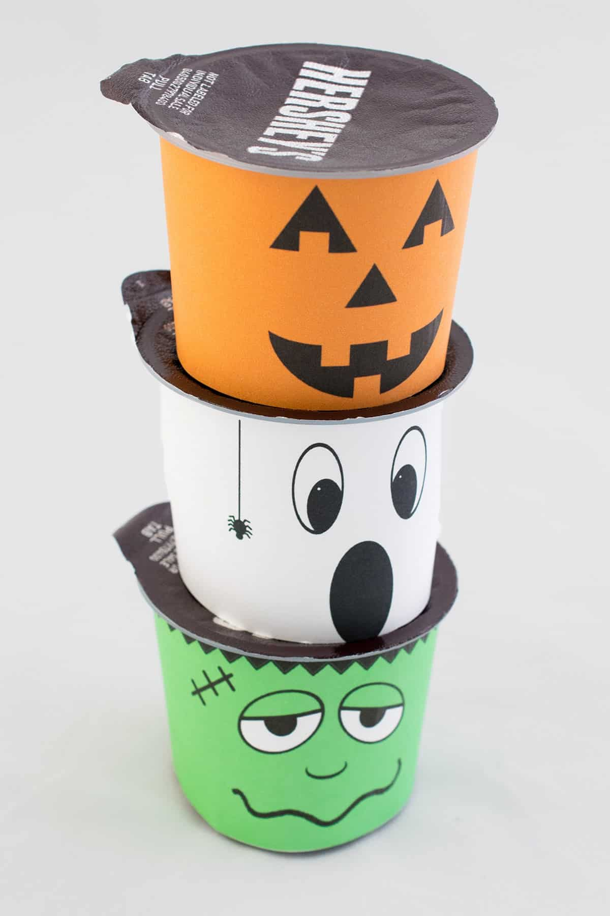 Three stacked Hershey's pudding cups with Halloween printable wrappers-Frankenstein, ghost, and pumpkin with white background.