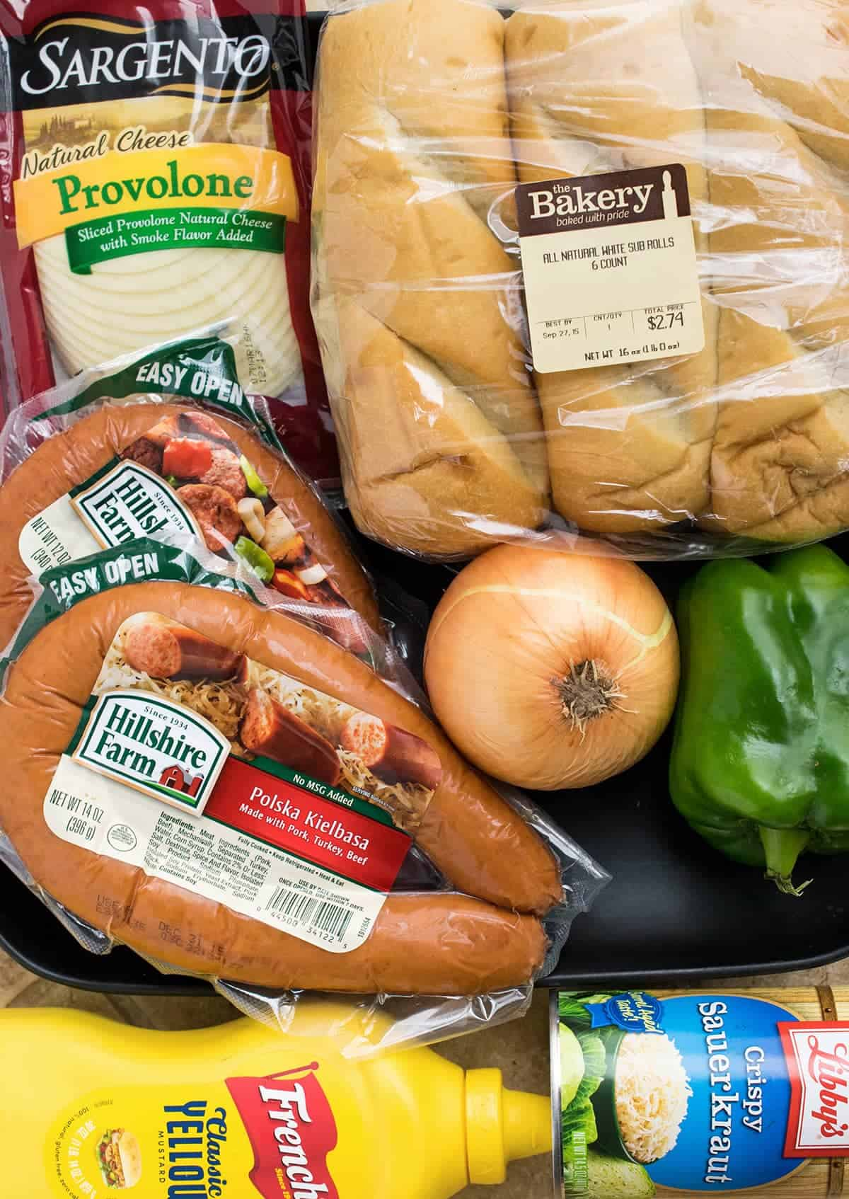 Ingredients for polish sausage sandwiches including kielbasa, hoagie rolls, peppers, onions, slices provolone, sauerkraut, and mustard.