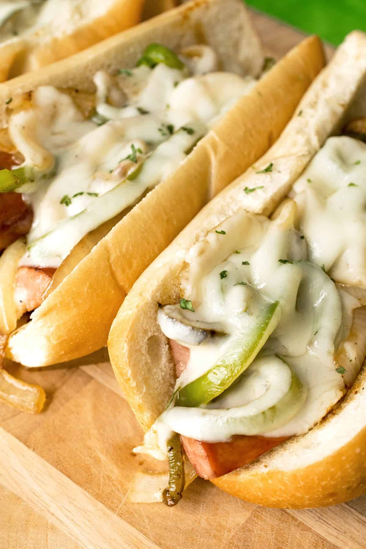 Kielbasa sandwiches with peppers, onions, and melted provolone on wooden surface.