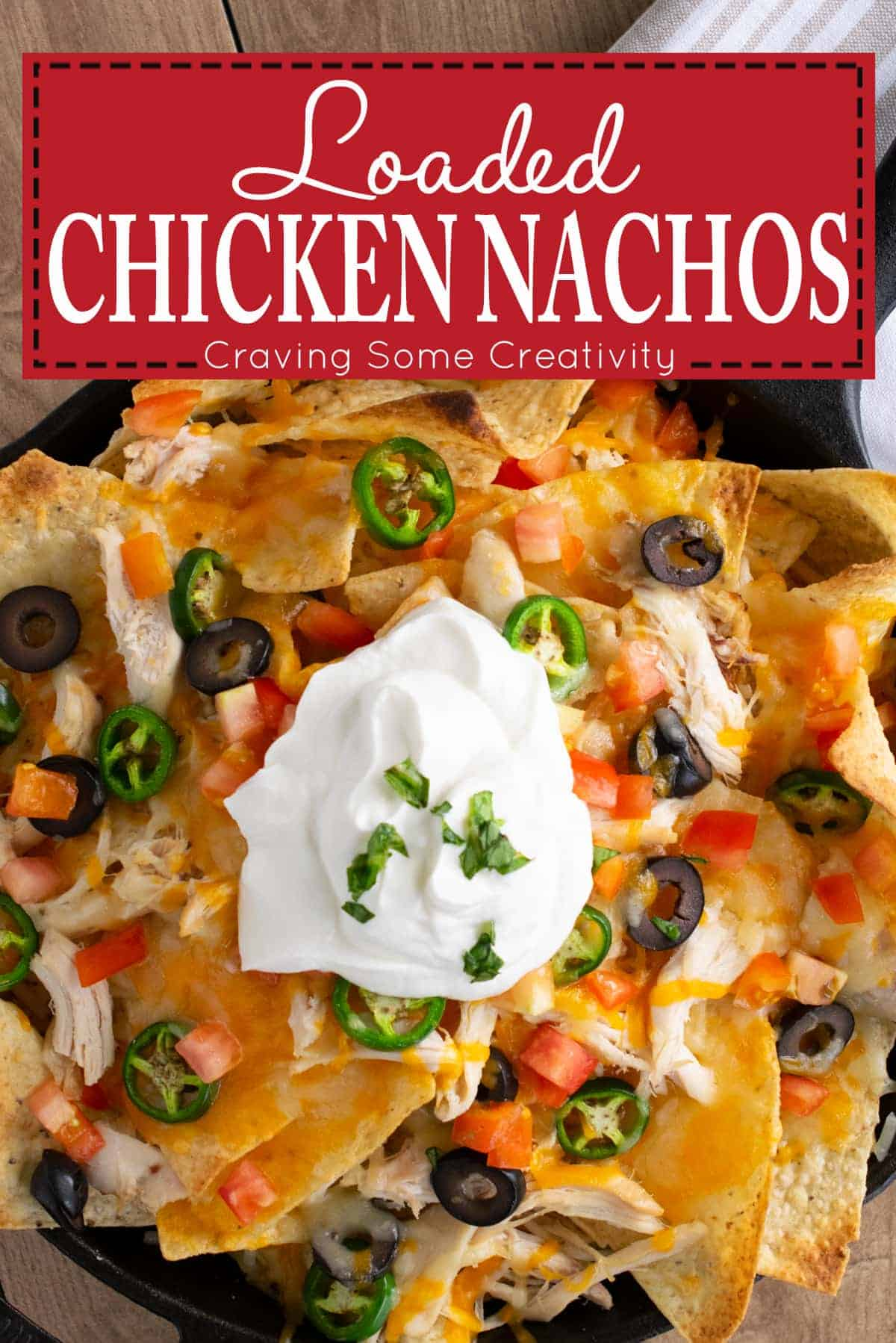 Loaded Chicken nachos topped with melted cheese, black olives, diced tomatoes, jalapenos, and sour cream in cast iron skillet with post title.