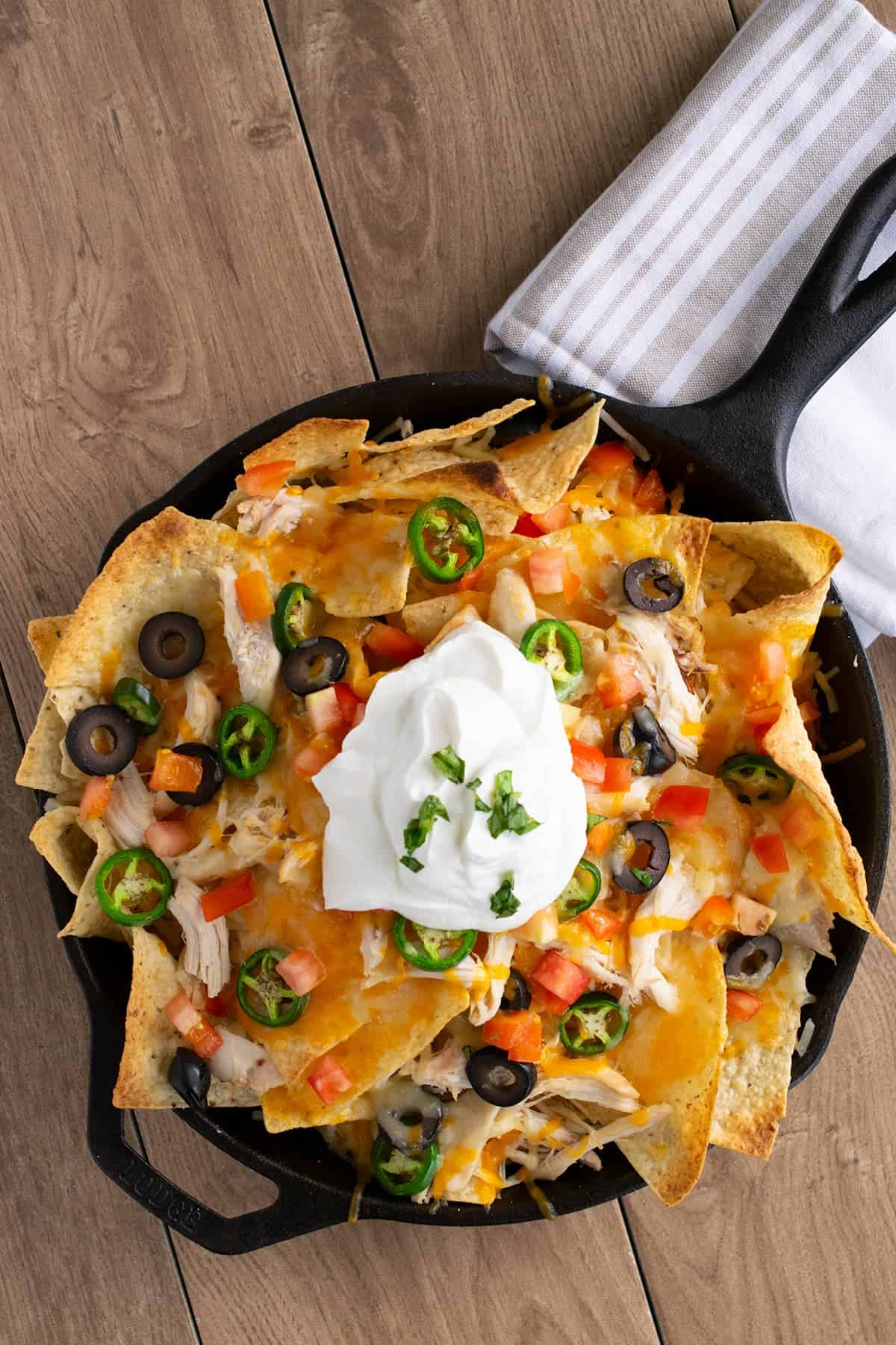 Loaded Chicken nachos topped with melted cheese, black olives, diced tomatoes, jalapenos, and sour cream in cast iron skillet on wood table next to kitchen towel.