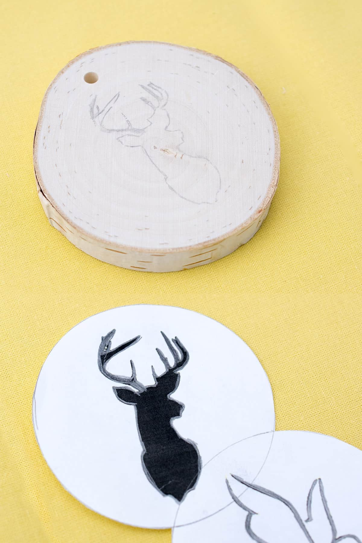 Round wood slice ornament with deer head image next to round paper with same image on yellow surface.