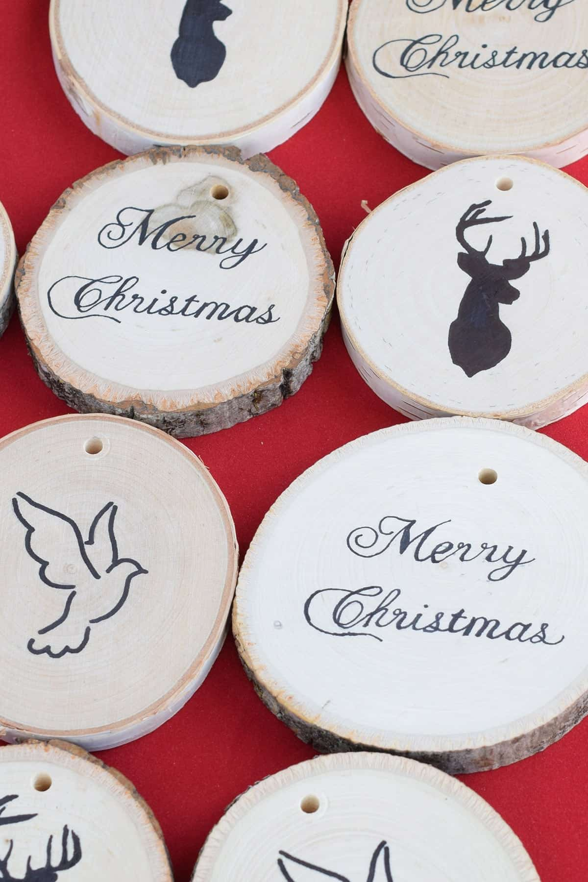 Two rows of wood slice ornaments with Christmas themed image transfers on red surface.