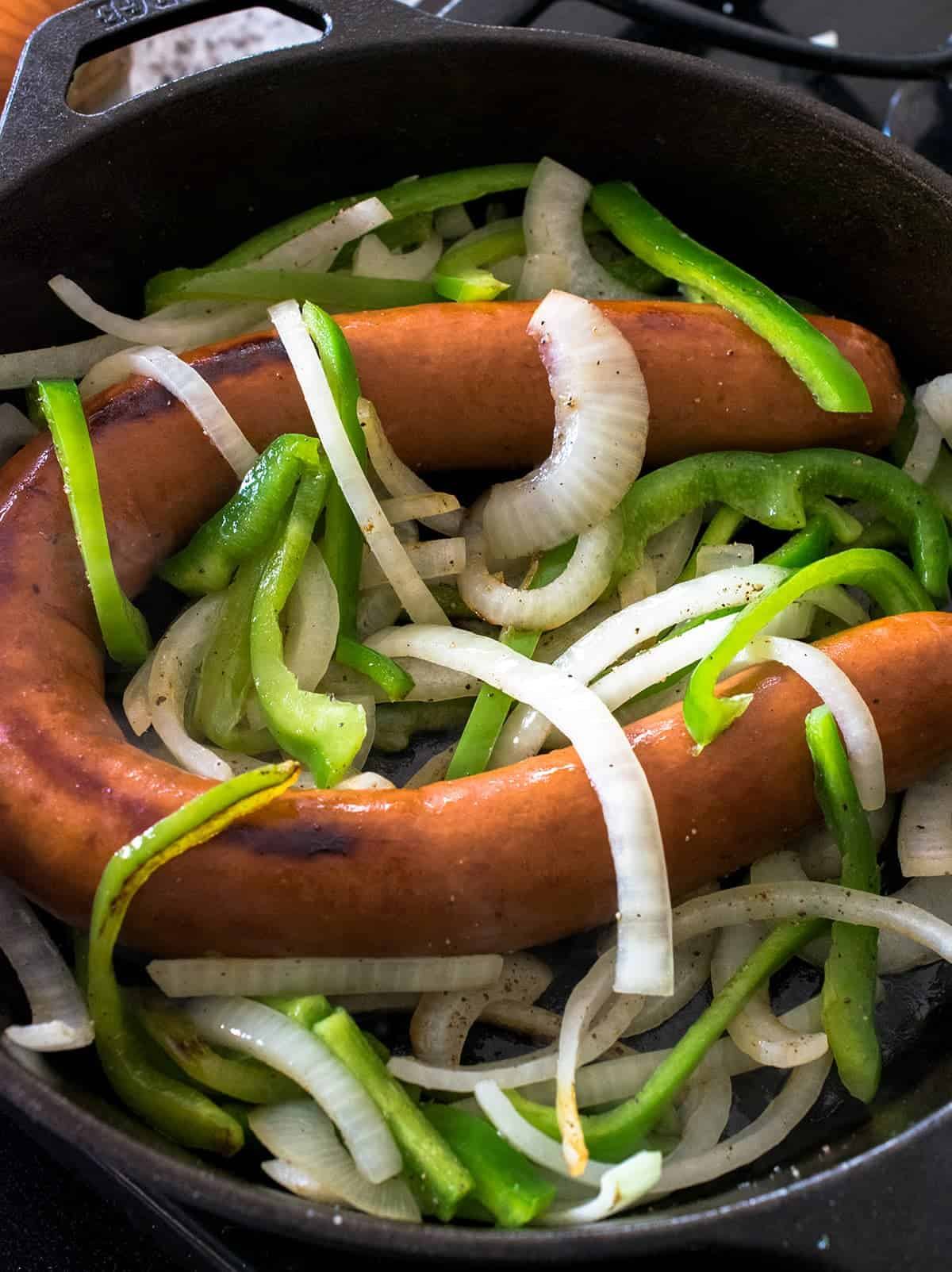 Cast iron skillet with whole kielbasa sausage and slice onions and green peppers.