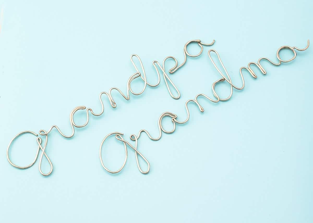 DIY wire art- Grandma and Grandpa written in cursive wire art on blue surface.