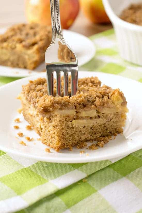 Apple Cinnamon Coffee Cake with Streusel Topping - on white plate with fork placed in the middle on green towel next to apples.