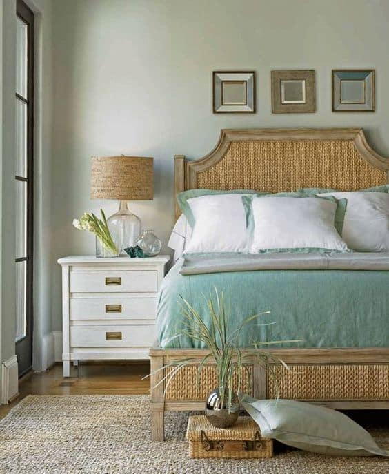 Coastal bedroom with wood and wicker bed, teal bedding with white pillows, soft green walls with framed mirrors, and white side table.
